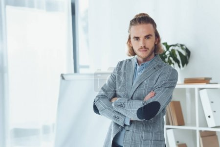 businessman standing with crossed arms and looking at camera