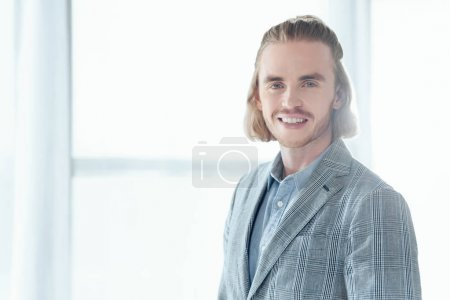 Photo for Smiling businessman standing and looking at camera - Royalty Free Image