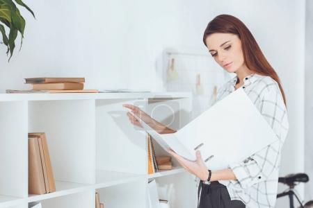 Attraktive Geschäftsfrau schaut sich Unterlagen in Ordner an