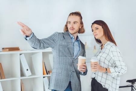 Photo pour Homme d'affaires pointant sur quelque chose à son collègue pendant la pause café - image libre de droit