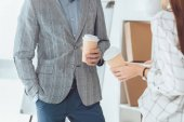 cropped image of male and female colleagues having coffee break in office