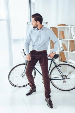 handsome businessman leaning on bicycle and looking away