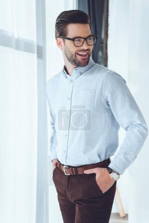 smiling businessman with hands in pockets looking away