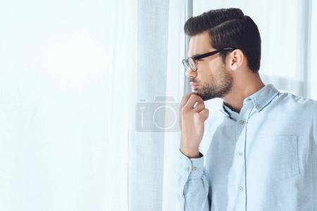 side view of thoughtful handsome businessman looking away