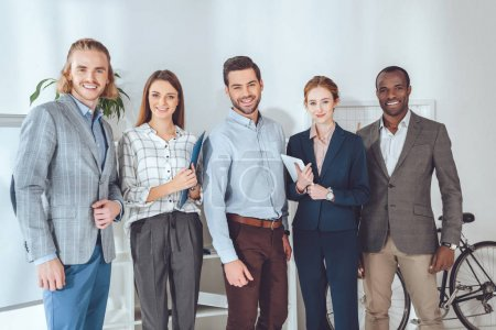 smiling multicultural businesspeople standing and looking at camera