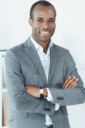 smiling african american man with crossed arms looking at camera