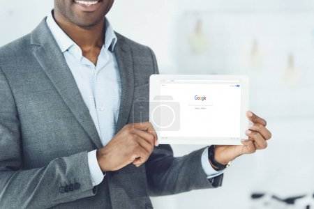 cropped image of smiling african american man showing tablet with loaded google page