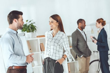 smiling multicultural businesspeople standing and talking on office