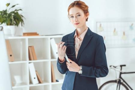 Photo pour Femme d'affaires souriante tenant la tablette et regardant la caméra - image libre de droit