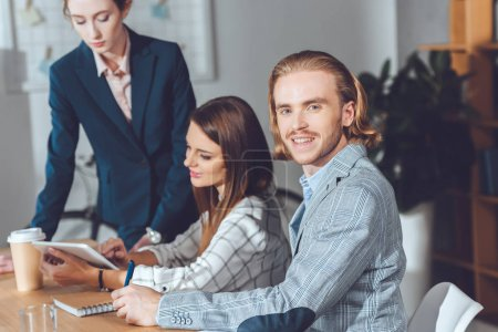 handsome businessman looking at camera during meeting