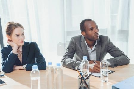 multicultural businesspeople sitting at meeting and looking away