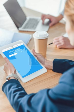Photo for Cropped image of woman holding digital tablet while sitting at table - Royalty Free Image