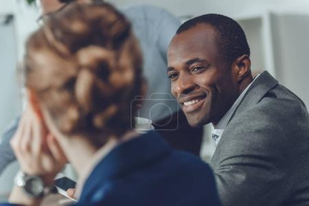 african man smiling to woman sitting at table at office space