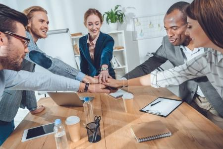 business team shaking hands over table at office space