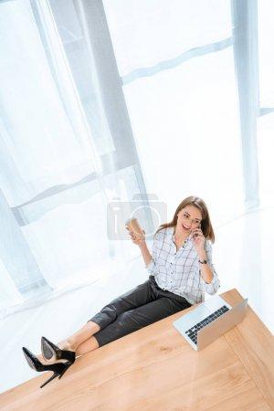 Photo pour Femme heureuse en chemise assis sur chaise avec les jambes sur la table contre ordinateur portable tout en prenant la parole au téléphone - image libre de droit