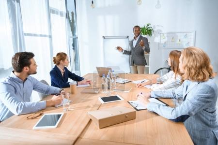Photo pour Homme africain debout contre la table et parler à l'équipe à l'espace de bureau - image libre de droit