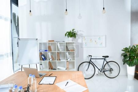 view of empty office interior with table and bicycle against wall