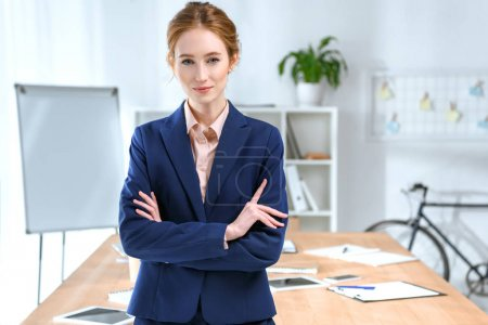businesswoman with arms crossed looking at camera at office space