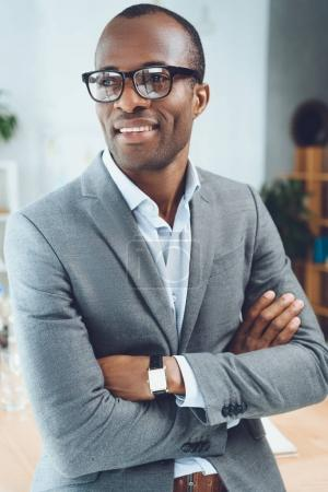 smiling african man with arms crossed looking away at office space