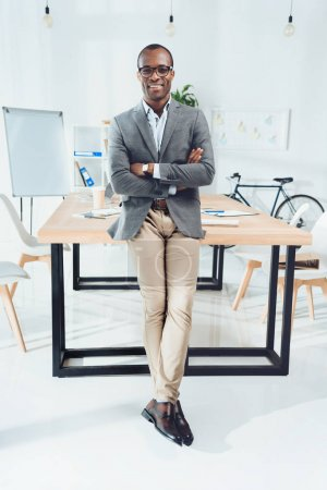 smiling african man leaning on table with arms crossed at office space