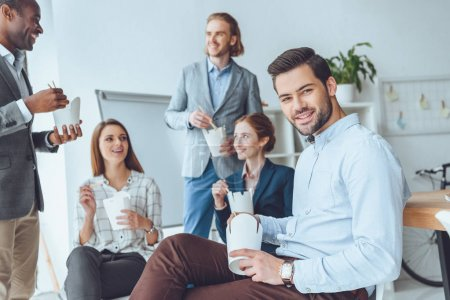 smiling businesspeople eating from paper boxes at office space