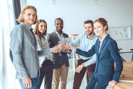 business team celebrating with beverage in glasses at office space