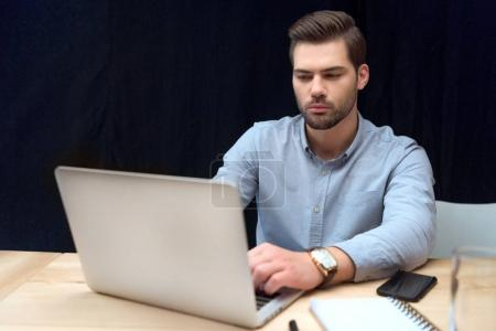 caucasian man in blue shirt sitting and using laptop on table