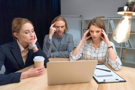 business team have discussion while sitting at table with laptop