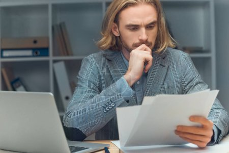 pensive caucasian man holding paper while sitting at table