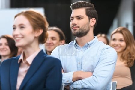 Caucasian man in blue shirt looking away while sitting at meeting