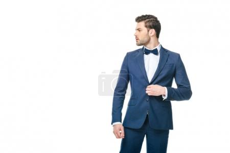 portrait of young man in fashionable suit looking away isolated on white