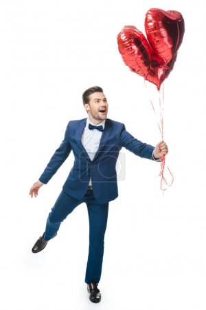 Photo for Happy young man with heart shaped balloons isolated on white - Royalty Free Image