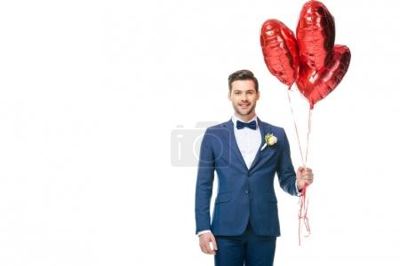 portrait of happy young groom with heart shaped balloons isolated on white