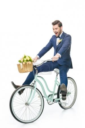 happy groom in suit riding retro bicycle with wedding bouquet in basket isolated on white