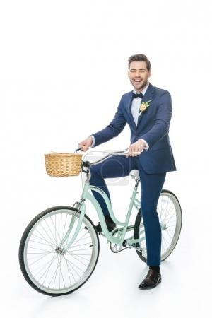 cheerful groom riding retro bicycle isolated on white