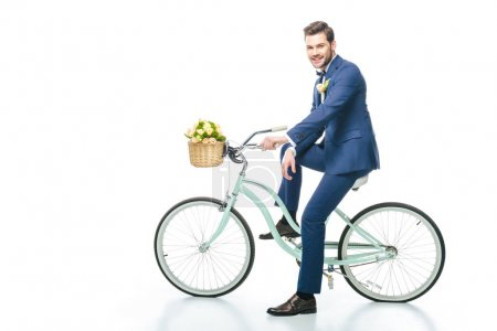 groom in suit sitting on retro bicycle with wedding bouquet in basket isolated on white
