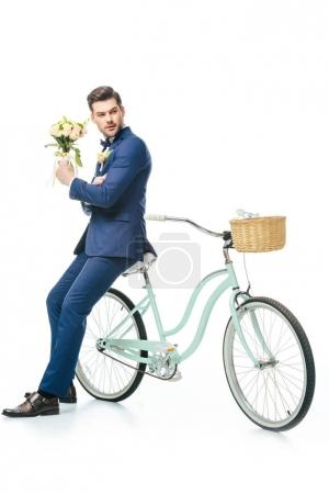 Photo for Stylish groom with wedding bouquet leaning on retro bicycle isolated on white - Royalty Free Image