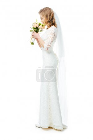 side view of attractive bride in wedding dress and veil with bouquet of flowers isolated on white