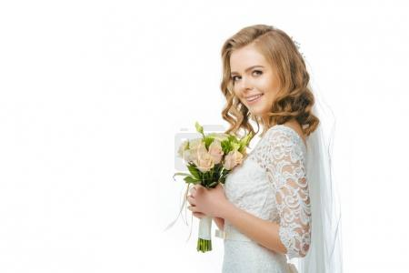 side view of smiling bride in wedding dress and veil with bouquet of flowers isolated on white