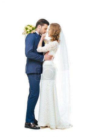 vue latérale du couple de jeune mariée en regardant l'autre isolé sur blanc