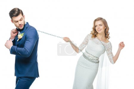 young groom holding young bride on chain isolated on white