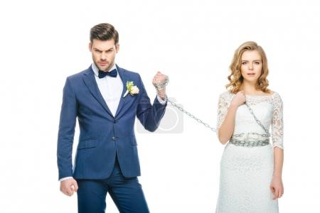 Photo for Groom holding shocked young bride on chain isolated on white - Royalty Free Image