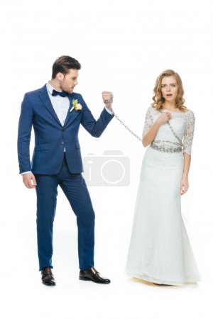 groom holding shocked young bride on chain isolated on white
