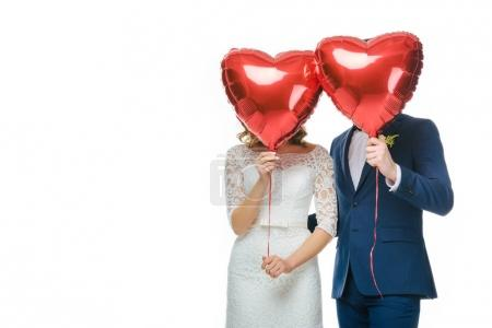 Photo for Wedding couple covering faces with red heart shaped balloons isolated on white - Royalty Free Image