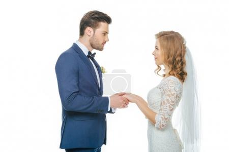 side view of beautiful wedding couple holding hands and looking at each other isolated on white