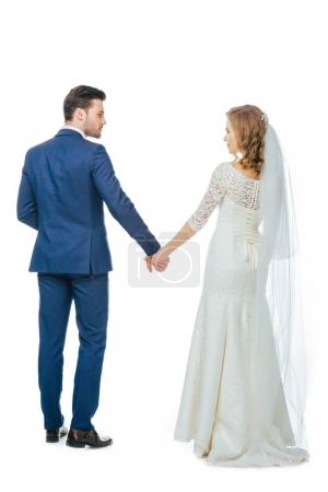 back view of beautiful wedding couple holding hands isolated on white