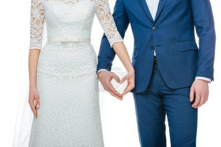 Photo pour Vue partielle du couple de mariage montrant le symbole de coeur fait de mains ensemble isolé sur blanc - image libre de droit