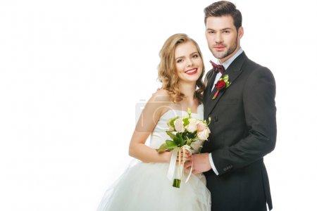 Porträt einer lächelnden Braut mit Brautstrauß und Bräutigam in der Nähe isoliert auf Weiß