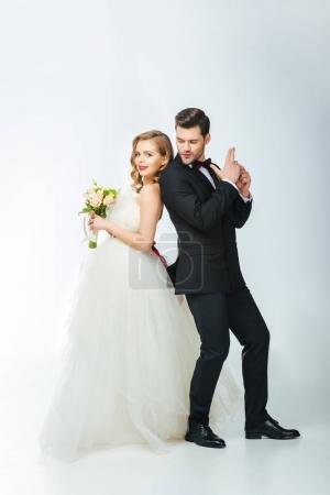bride and groom standing back to back together