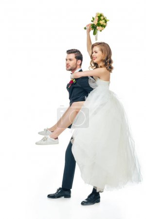side view of happy bride and groom piggybacking together isolated on white